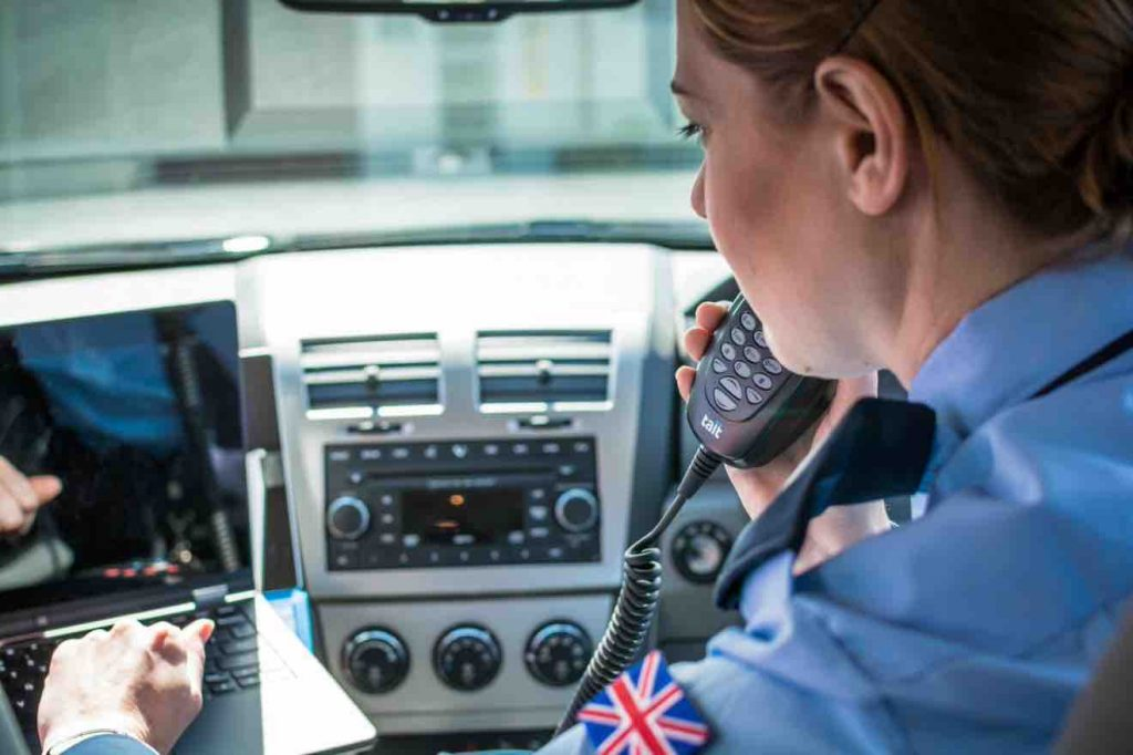 Police officer making a call on a Tait TM8 mobile radio