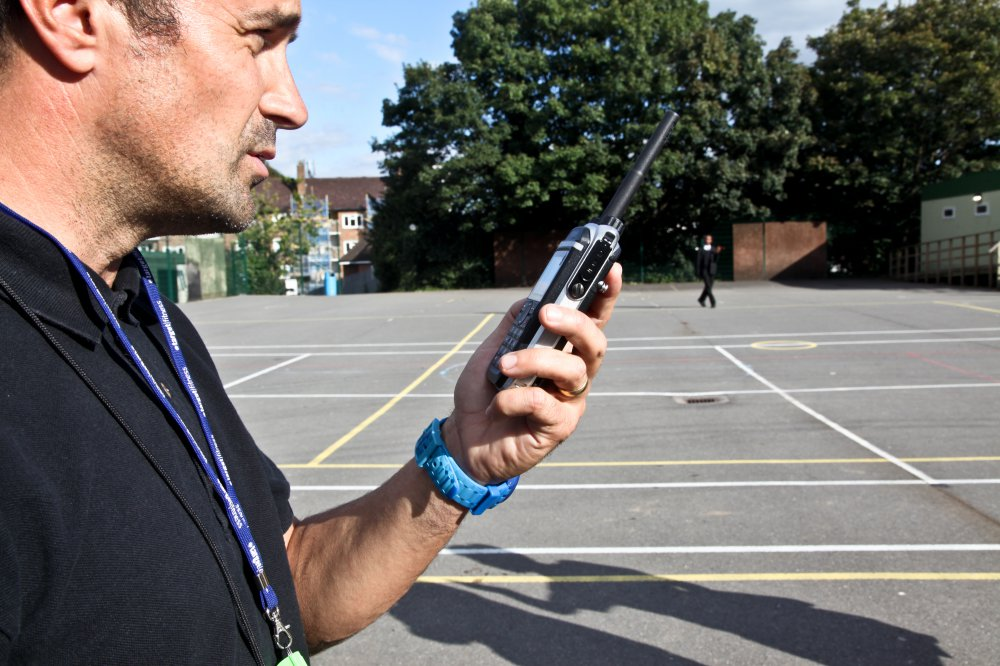 Hytera PD685 DMR walkie talkie in use at a school playground
